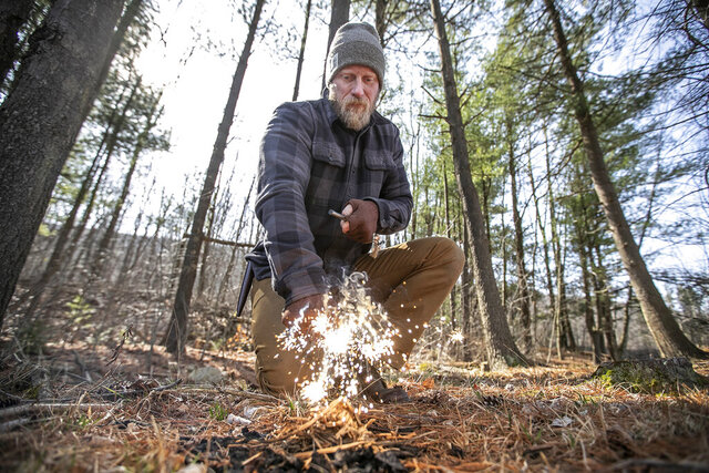 In this March 18, 2020, photo, using the back of his hunting knife, Dan Wowak, scrapes downward on a ferro rod, which creates a very hot, glowing spark that will ignite the dry grass he has on the ground and start the process of building a fire in the woods, in Ringtown, Pa. Wowok is a survival guru who runs camps for teaching the skills of survival and has a YouTube channel where he shares his knowledge and skills. (Michael Bryant/The Philadelphia Inquirer via AP)