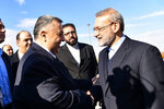 In this photo released by the Syrian official news agency SANA, Speaker of the People's Council of Syria, Hammouda Sabbagh, left, receives Iran's Parliament Speaker Ali Larijani on his arrival to the airport, in the Syrian capital Damascus, Sunday, Feb. 16, 2020. (SANA via AP)