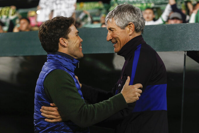 FILE - In this Sunday, Feb. 9, 2020 file photo, Barcelona's head coach Quique Setien, right, salutes Betis' head coach Rubi during La Liga soccer match between Betis and Barcelona at the Benito Villamarin stadium in Seville, Spain. Real Betis has fired coach Rubi after the team's third consecutive setback since the Spanish league resumed.The decision was announced early Sunday, June 21, 2020 a few hours after the team lost 1-0 at Athletic Bilbao. (AP Photo/Miguel Morenatti, File)