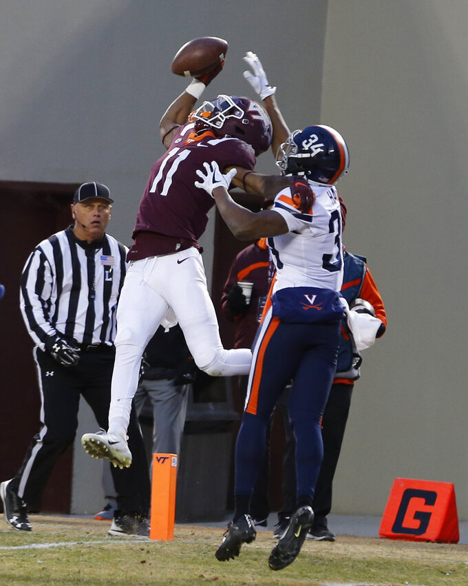 Virginia Tech wide receiver Tre Turner (11) catches a touchdown pass in front of Virginia cornerback Bryce Hall (34) during the first half of an NCAA college football game in Blacksburg, Va., Friday, Nov. 23, 2018. (AP Photo/Steve Helber)