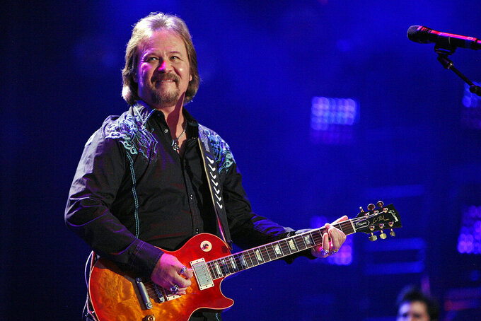 FILE - In this Friday, June 6, 2014 file photo, Travis Tritt performs during the CMA Fest at LP Field in Nashville, Tenn. Tritt, who canceled shows at venues that required a COVID-19 vaccine or mask-wearing, was set to sing the national anthem before Game 6 of the NL Championship Series on Saturday night, Oct. 23, 2021. The Braves' 41,000-seat stadium, Truist Park, has allowed full capacity most of the season with no requirements for vaccinations, negative tests or mask-wearing from fans.  (Photo by Wade Payne/Invision/AP, File)
