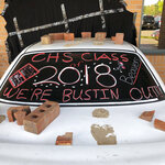 This photo taken Wednesday, May 16, 2018, and provided by Ritchie Narges shows what looks to be a car that crashed into the principal's office at Cumberland High School in Cumberland, Wis., but is actually an illusion created for a senior class prank. Students at the school used a junk car, some bricks, some tape and a black tarp to make it look like the car had crashed into their school. The police department wrote on Facebook that it was