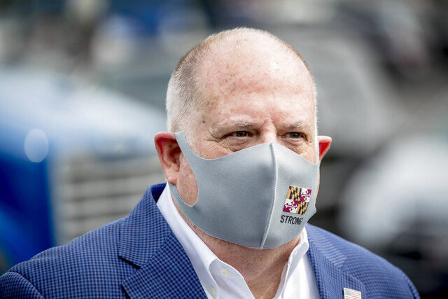 FILE - In this Friday, May 15, 2020, file photo, Maryland Gov. Larry Hogan wears a mask with the Maryland state flag on it following a tour of Coastal Sunbelt Produce in Laurel, Md. A federal judge on Wednesday, May 20, rejected a request to issue a temporary restraining order sought by people challenging Hogan's stay-at-home order in the face of the COVID-19 pandemic. (AP Photo/Andrew Harnik, File)