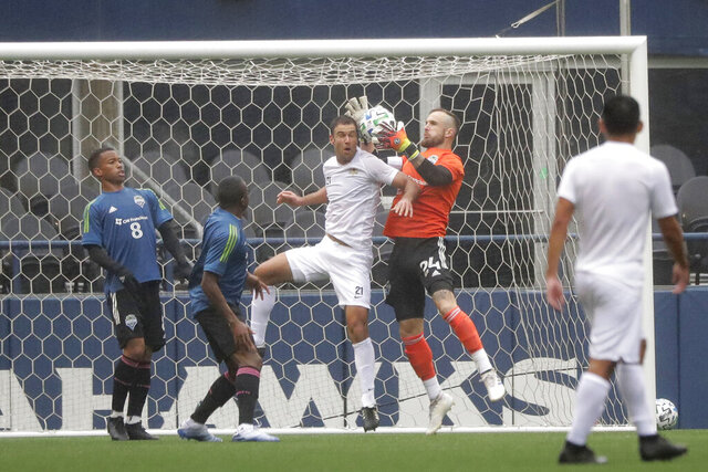 Seattle Sounders goalkeeper Stefan Frei, second from right, grabs the ball next to Sacramento Republic FC defender Dekel Keinan during the first half of a soccer scrimmage Wednesday, Feb. 5, 2020, in Seattle. (AP Photo/Ted S. Warren)