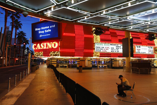 FILE - In this April 19, 2020, file photo, a lone security guard watches over casinos shuttered due to the coronavirus outbreak in Las Vegas. Nevada gambling regulators said Tuesday, May 26, 2020, they may require the state's shuttered casinos to test all