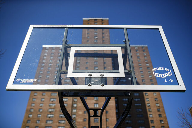 FILE - In this March 26, 2020, file photo, basketball backboards stand without hoops after city officials had them removed to reduce gatherings at Holcombe Rucker Park in New York. The COVID-19 pandemic has left the New York street ball scene quiet. While the city is set to slowly begin reopening this month, recreation activities aren't set to be addressed for several weeks. It's left open the possibility that New York's hallowed outdoor courts such as Rucker Park, all as much a part of New York's basketball culture as the Knicks and Madison Square Garden, could remain silenced into summer. (AP Photo/John Minchillo, File)