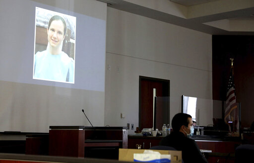 Mark Gooch, 22, sits below an image of Sasha Krause shown on a screen during his trial at the Coconino County Superior Court in Flagstaff, Ariz., on Friday, Sept. 24, 2021. Gooch is charged with first-degree murder in Krause's death in early 2020. (Jake Bacon/Arizona Daily Sun via AP)