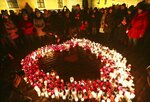 People stand by a heart shaped with candles as a tribute to slain President of Gdansk Pawel Adamowicz at the Square in the Old Town, Warsaw, Poland, Wednesday, Jan. 16, 2019.(AP Photo/Czarek Sokolowski)