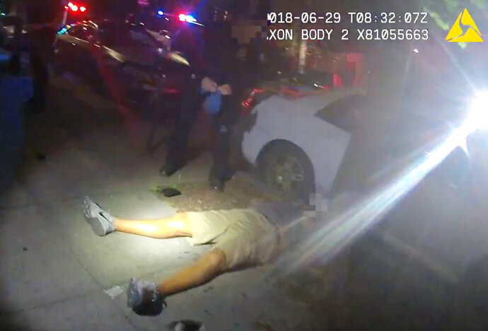 This June 29, 2018 video image from a police officer's body cam and provided by Portland State University shows Jason Washington after he was shot by Portland State University police officers in Portland, Ore.  Body camera video from two campus police officers shows they ordered the legally armed Washington to drop a gun before opening fire, killing him. (Portland State University via AP)