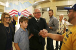 DFL gubernatorial candidate Tim Walz, center, his son Gus and his running mate, Peggy Flanagan, left,  greet supporters during their primary election night party at the Carpenters Union Hall in St. Paul, Minn., Tuesday, Aug. 14, 2018. (Anthony Souffle/Star Tribune via AP)