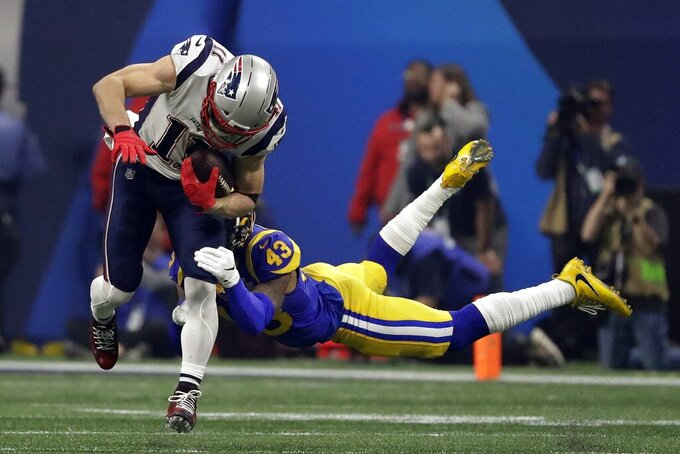New England Patriots' Julian Edelman (11) breaks a tackle by Los Angeles Rams' John Johnson III (43), during the second half of the NFL Super Bowl 53 football game Sunday, Feb. 3, 2019, in Atlanta. (AP Photo/Jeff Roberson)