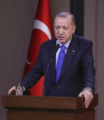 Turkish President Recep Tayyip Erdogan speaks to reporters before a visit to the United States, in Ankara, Turkey, Tuesday, Nov. 12, 2019. Erdogan warned European nations Tuesday that his country could release all the Islamic State group prisoners it holds and send them to Europe, in response to EU sanctions over Cyprus.(Presidential Press Service via AP, Pool)
