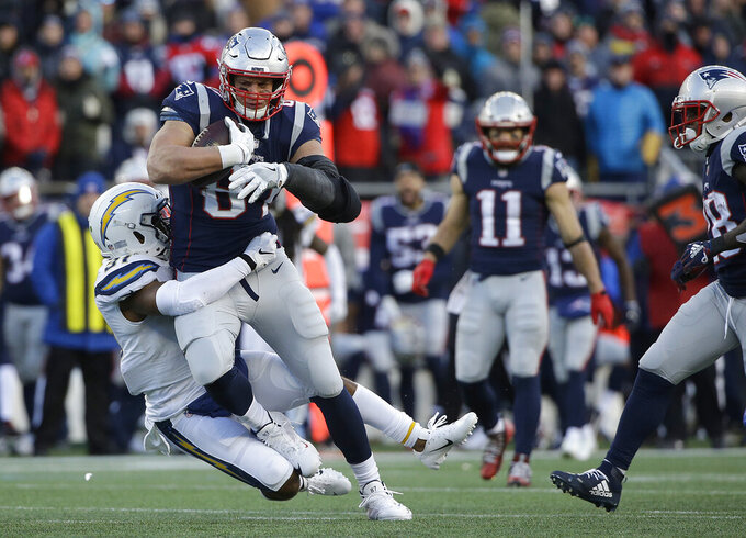 New England Patriots tight end Rob Gronkowski is tackled by Los Angeles Chargers defensive back Adrian Phillips after catching a pass during the second half of an NFL divisional playoff football game, Sunday, Jan. 13, 2019, in Foxborough, Mass. (AP Photo/Steven Senne)