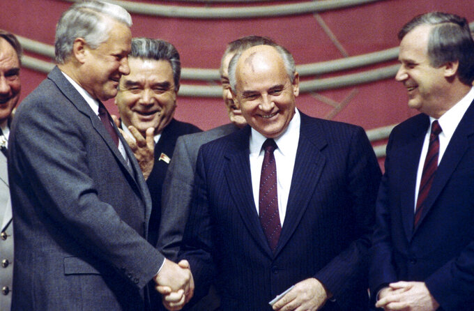 FILE - In this Thursday, Nov. 8, 1990 file photo, in a spontaneous and rare moment of accord between the Soviet Union's most popular politicians, rivals Boris Yeltsin, left, and Mikhail Gorbachev shake hands at a Kremlin ceremony on the 73rd anniversary of the Bolshevik Revolution in Moscow. Former Soviet leader Mikhail Gorbachev turned 90 on Tuesday March 2, 2021,, receiving greetings from the Kremlin and global leaders while Russians remained divided over his legacy. (AP Photo/Alexander Zemlianichenko, File)