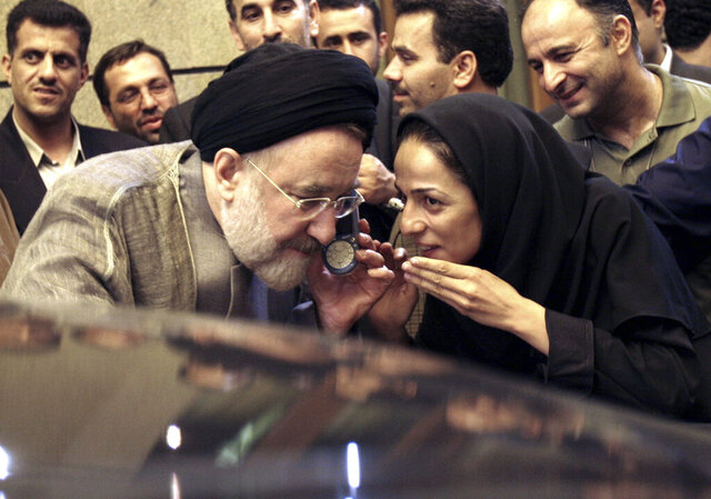 FILE - In this July 13, 2005, file photo, outgoing reformist Iranian President Mohammad Khatami talks on the phone with the mother of female journalist Masih Alinejad, right, after meeting with journalists in Tehran, Iran. Alinejad, famous for her campaign against the Islamic Republic's mandatory headscarf, or hijab, for women filed a lawsuit on Monday, Dec. 2, 2019, in U.S. federal court against Iran, alleging a government-led harassment campaign targets her and her family. (AP Photo/Hasan Sarbakhshian, File)
