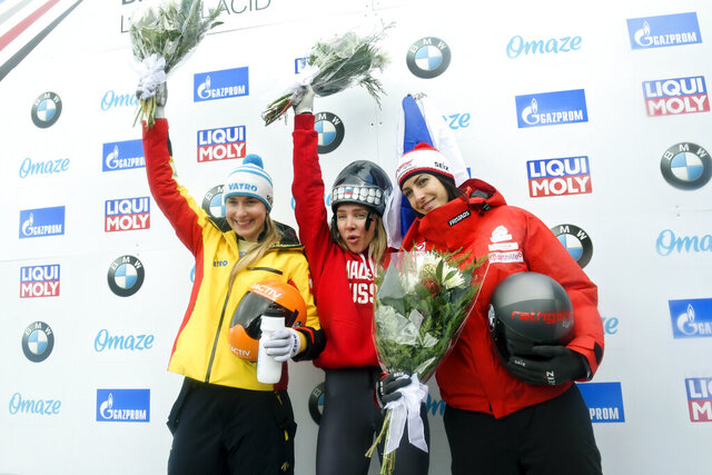 Winner Elena Nikitina, center, of Russia, celebrates on the podium with second place finisher Jacqueline Loelling, left, of Germany, and third place finisher Janine Flock, left, of Austria, following the women's skeleton World Cup race in Lake Placid, N.Y., on Friday, Dec. 13, 2019. (AP Photo/Hans Pennink)
