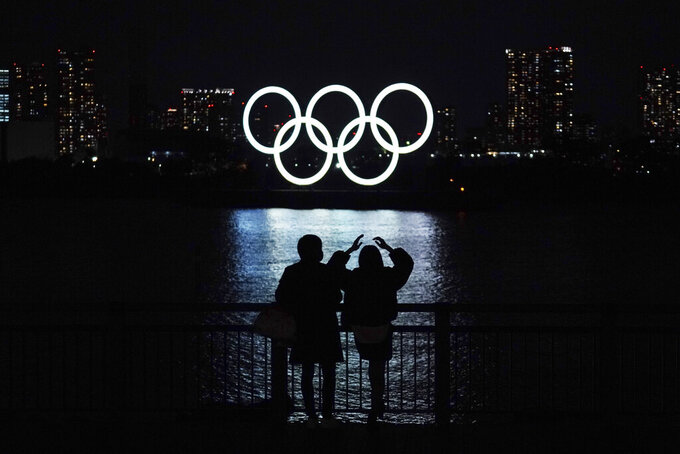 FILE - In this Dec. 1, 2020, file photo, a man and a woman look at the Olympic rings float in the water in the Odaiba section in Tokyo. The U.S. Olympic and Paralympic Committee heeded calls from American athletes, announcing Thursday, Dec. 10, 2020, that it won't sanction them for raising their fists or kneeling on the medals stand at next year's Tokyo Games and beyond. (AP Photo/Eugene Hoshiko, File)