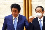 """FILE - In this May 4, 2020, file photo, then Japan's Prime Minister Shinzo Abe, left, gestures by then Chief Cabinet Secretary Yoshihide Suga at the end of a news conference at the prime minister's office in Tokyo. Among the challenges awaiting newly appointed Japanese Prime Minister Suga is the urgent challenge of how to keep the world's third largest economy growing as its population ages and shrinks. Suga vowed to stick with the """"Abenomics"""" playbook of cheap credit and stimulus spending, but has yet to articulate a vision for the future for a nation wary of the sweeping changes needed to keep the economy growing. (AP Photo/Eugene Hoshiko, Pool, File)"""
