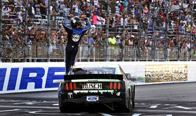 Kevin Harvick raises his arms toward fans after winning a NASCAR Cup Series auto race at New Hampshire Motor Speedway in Loudon, N.H., Sunday, July 21, 2019. (AP Photo/Charles Krupa)