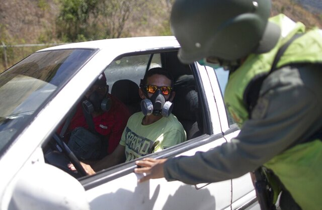 A man wearing a mask talks to a solider checking vehicles entering  Caracas, Venezuela, Monday, March 16, 2020. President Nicolás Maduro ordered Sunday residents in the capital of Caracas and six states to stay home under a quarantine in a bid to control the spread of the coronavirus According to the World Health Organization, most people recover in about two to six weeks from the virus, depending on the severity of the illness. (AP Photo/Ariana Cubillos)