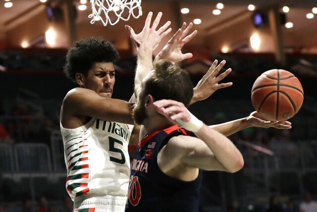 Miami guard Harlond Beverly (5) attempts to pass the ball as Virginia forward Jay Huff (30) defends during the second half of an NCAA college basketball game, Wednesday, March 4, 2020, in Coral Gables, Fla. Virginia won 46-44. (AP Photo/Lynne Sladky)