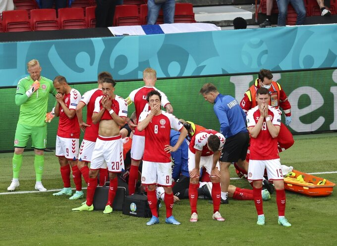 Denmark's players react as their teammate Christian Eriksen lays injured on the ground during the Euro 2020 soccer championship group B match between Denmark and Finland at Parken stadium in Copenhagen, Denmark, Saturday, June 12, 2021. (Wolfgang Rattay/Pool via AP)