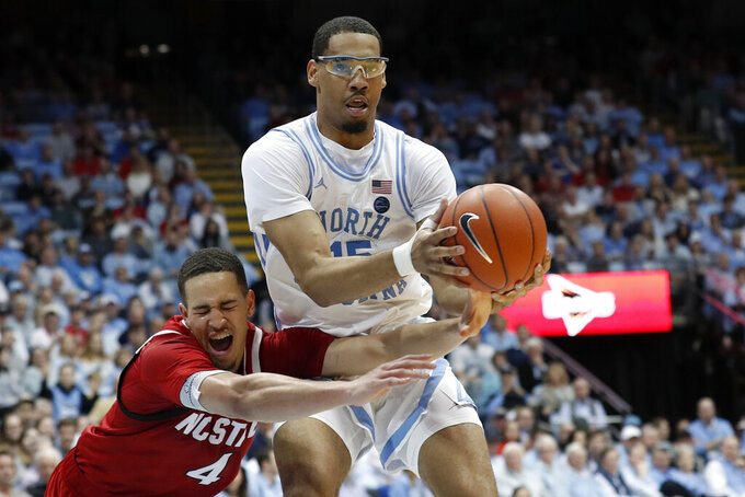 North Carolina State forward Jericole Hellems (4) reaches for the ball against North Carolina forward Garrison Brooks during the first half of an NCAA college basketball game in Chapel Hill, N.C., Tuesday, Feb. 25, 2020. (AP Photo/Gerry Broome)