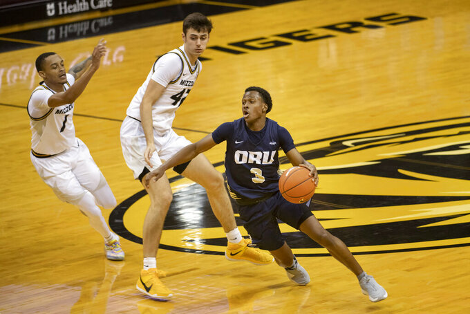Oral Roberts' Max Abmas, right, dribbles around Missouri's Parker Braun, center, and Xavier Pinson, left, during the first half of an NCAA college basketball game Wednesday, Nov. 25, 2020, in Columbia, Mo. (AP Photo/L.G. Patterson)
