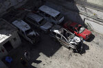 Damaged cars are parked near the site of Wednesday's attack in Kabul, Afghanistan, Thursday, May 9, 2019. Taliban fighters attacked the offices of a U.S.-based aid organization in the Afghan capital on Wednesday, setting off a huge explosion and battling security forces in an assault, the Interior Ministry said. (AP Photo/Rahmat Gul)