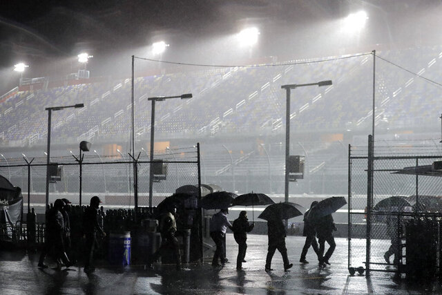 People leave the infield at Darlington Raceway after the NASCAR Xfinity series auto race was postponed because of rain Tuesday, May 19, 2020, in Darlington, S.C. (AP Photo/Brynn Anderson)