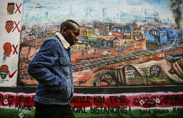 A man walks past an informational mural with messages in English and Swahili warning people about the dangers of the new coronavirus and how to prevent transmission, painted by youth artists from the Uweza Foundation, in the Kibera slum, or informal settlement, of Nairobi, Kenya Wednesday, July 8, 2020. Africa now has more than a half-million confirmed coronavirus cases, according to the Africa Centers for Disease Control and Prevention, but the true number of cases among Africa's 1.3 billion people is unknown as its 54 countries face a serious shortage of testing materials for the virus. (AP Photo/Brian Inganga)