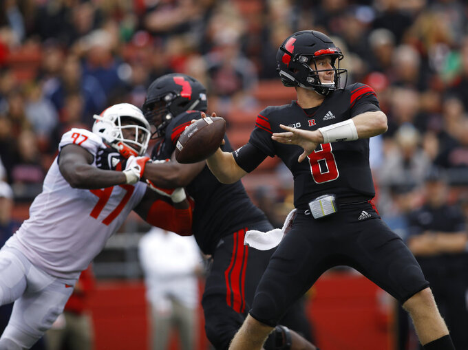 Rutgers quarterback Artur Sitkowski looks for a receiver as Illinois defensive lineman Bobby Roundtree, left, is blocked during the first half of an NCAA college football game Saturday, Oct. 6, 2018, in Piscataway, N.J. (AP Photo/David Boe)