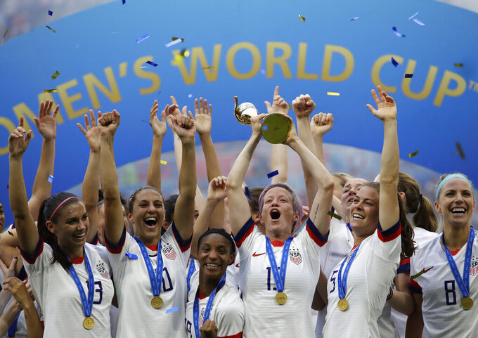 FILE - In this July 7, 2019, file photo,  United States' Megan Rapinoe lifts up a trophy after winning the Women's World Cup final soccer match between US and The Netherlands at the Stade de Lyon in Decines, outside Lyon, France. The  global players' association released its report on the state of  women's soccer, after warning that the coronavirus  outbreak could have a disastrous impact following the gains of last summer's Women's World Cup.  (AP Photo/Alessandra Tarantino, File)