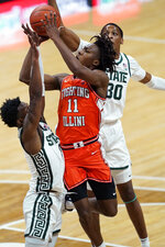 Illinois guard Ayo Dosunmu (11) shoots over the defense of Michigan State guard Rocket Watts (2) and forward Marcus Bingham Jr. (30) during the first half of an NCAA college basketball game, Tuesday, Feb. 23, 2021, in East Lansing, Mich. (AP Photo/Carlos Osorio)