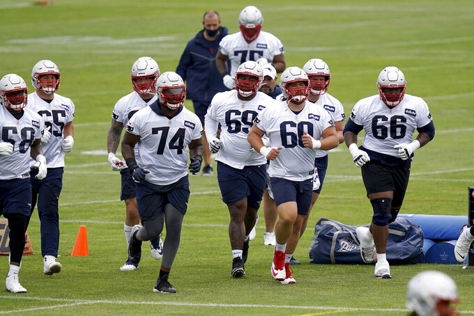New England Patriots center David Andrews (60) leads his teammates across a field during NFL football practice in Foxborough, Mass., Friday, June 4, 2021. (AP Photo/Mary Schwalm)