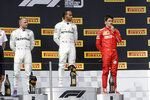 Mercedes driver Lewis Hamilton, center, of Britain, winner of the French Formula One Grand Prix, stands on the podium with second placed Mercedes driver Valtteri Bottas, left, of Finland, and third placed Ferrari driver Charles Leclerc, of Monaco, at the Paul Ricard racetrack in Le Castellet, southern France, Sunday, June 23, 2019. (AP Photo/Claude Paris)