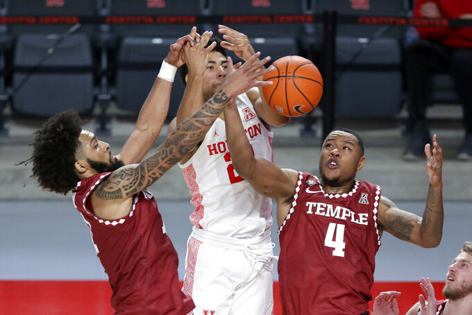 Temple guard Damian Dunn, left, and forward J.P. Moorman II (4) battle for a rebound with Houston guard Quentin Grimes, middle, during the first half of an NCAA college basketball game Tuesday, Dec. 22, 2020, in Houston. (AP Photo/Michael Wyke)