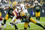 Green Bay Packers' Adrian Amos stops Washington Redskins' Adrian Peterson during the second half of an NFL football game Sunday, Dec. 8, 2019, in Green Bay, Wis. (AP Photo/Mike Roemer)