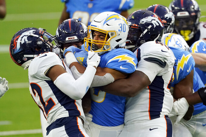 Los Angeles Chargers running back Austin Ekeler (30) is tackled by two Denver Broncos defenders during the second half of an NFL football game Sunday, Dec. 27, 2020, in Inglewood, Calif. (AP Photo/Ashley Landis)