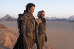 """This image released by Warner Bros. Entertainment shows Timothee Chalamet, left, and Rebecca Ferguson in a scene from the upcoming 2021 film """"Dune,"""" releasing on Oct. 22, (Chia Bella James/Warner Bros. Entertainment via AP)"""