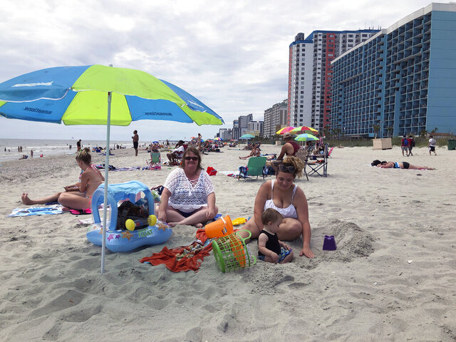 "Christy Kasler, center, from Ohio, enjoys a day at the beach, Thursday, June 18, 2020, while her daughter-in-law Cory plays with her grandson, Bentley, in Myrtle Beach, S.C. Across America, people are leaving their cares — and sometimes their masks — at home after months of worry about the virus as Southern states like South Carolina open hotels and restaurants and like Myrtle Beach advertise ""Yes, the beach is open!""  (AP Photo/Jeffrey Collins)"
