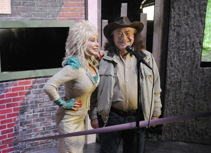 FILE - Country music legend Dolly Parton, left, stands with her uncle Bill Owens during a sneak peek preview at Dollywood in Pigeon Forge, Tenn., on March 22, 2013.  Owens, who was a mentor to his niece Dolly Parton and helped start her career in country music, has died. He was 85. Parton's publicist confirmed his death on Wednesday. (Curt Habraken/The Mountain Press via AP, File)