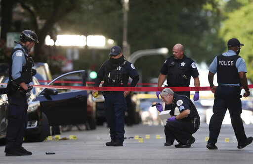 """FILE - In this Aug. 4, 2020, file photo, Chicago police investigate the scene of a shooing in Chicago. Five alleged gang members have been indicted on murder charges in last year's shooting death of Chicago rapper Carlton Weekly, also known as """"FBG Duck,"""" in the fashionable Gold Coast neighborhood, that prosecutors say was part of an ongoing violent effort to protect gang territories on the city's South Side, officials announced Wednesday, Oct. 13, 2021. (Chris Sweda/Chicago Tribune via AP, File)"""