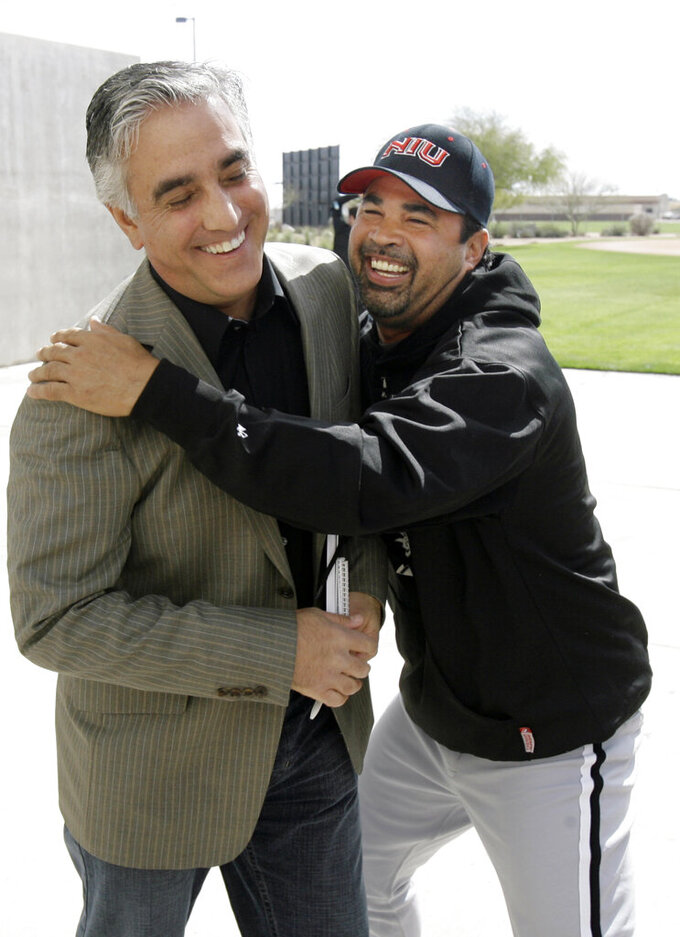 FILE - In this Saturday, Feb. 16, 2008, file photo, Chicago White Sox manager Ozzie Guillen, right, jokes with ESPN's Pedro Gomez after a news conference during the first day of baseball spring training for pitchers and catchers, in Tucson, Ariz. Gomez, a longtime baseball correspondent for ESPN who covered more than 25 World Series, died Sunday, Feb. 7, 2021. He was 58. (AP Photo/M. Spencer Green, File)