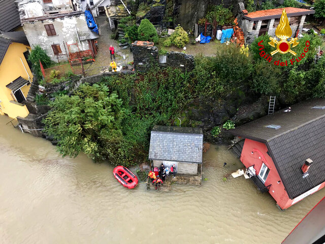 In this image made available Sunday, Oct. 4, 2020, firefighters evacuate people from a house amidst flooding in the town of Ornavasso, in the northern Italian region of Piedmont. (Firefighter Vigili del Fuoco via AP)