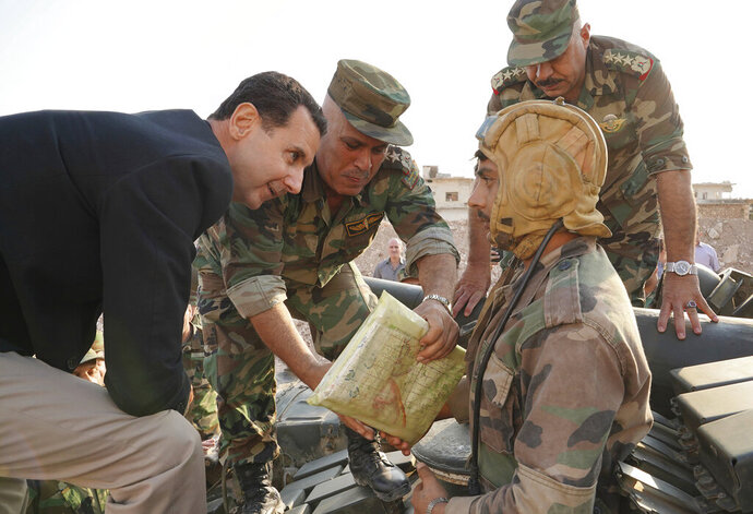 In this photo released on the official Facebook page of the Syrian Presidency, Syrian President Bashar Assad, left, speaks with Syrian troops during his visit to the strategic town of Habeet, in the northwestern province of Idlib, Syria, Tuesday, Oct. 22, 2019. On Tuesday, Assad called the Turkish President Recep Tayyip Erdogan a