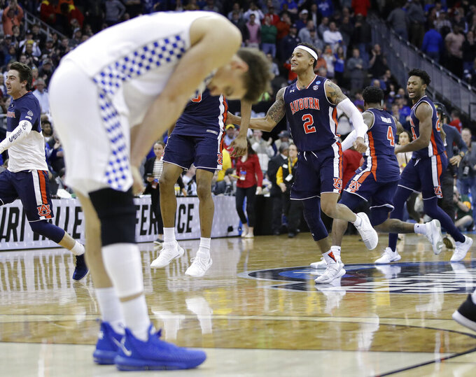 Auburn's Bryce Brown (2) and Anfernee McLemore, right, celebrate as Kentucky's Reid Travis, left, stands on the court following the Midwest Regional final game in the NCAA men's college basketball tournament Sunday, March 31, 2019, in Kansas City, Mo. Auburn won 77-71 in overtime. (AP Photo/Charlie Riedel)
