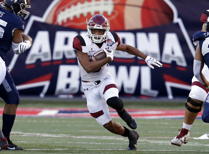 FILE - New Mexico State running back Larry Rose III (3) carries the ball in the second half during the Arizona Bowl NCAA college football game against Utah State in Tucson, Ariz., in this Friday, Dec. 29, 2017, file photo. The Arizona Bowl recently announced a partnership with Barstool Sports for its Dec. 31 game in Tucson, Arizona. The multiyear deal with the digital sports platform — notable for its occasional off-color humor and brash founder Dave Portnoy — not only includes naming rights but also broadcasting rights, which means the game won't be on ESPN or CBS.  (AP Photo/Rick Scuteri, File)