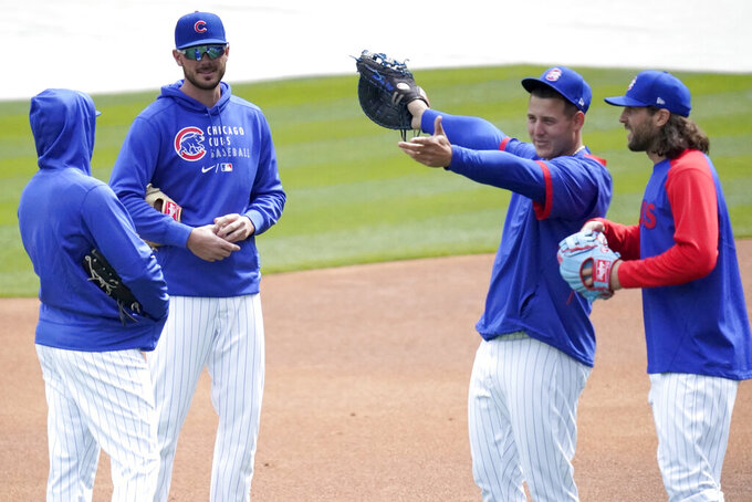 Chicago Cubs third baseman Kris Bryant, second from left, talks to Ian Happ, left, as first baseman Anthony Rizzo shows center fielder Jake Marisnick Wrigley Field during the team's last baseball workout Wednesday, March 31, 2021, before opening day Thursday, April 1, 2021, against the Pittsburgh Pirates in Chicago. (AP Photo/Charles Rex Arbogast)