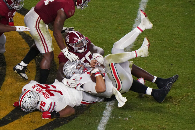 Ohio State quarterback Justin Fields is sacked by Alabama defensive lineman Christian Barmore during the second half of an NCAA College Football Playoff national championship game, Monday, Jan. 11, 2021, in Miami Gardens, Fla. (AP Photo/Wilfredo Lee)